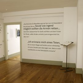 Wände mit Schrift beklebt, eine offene Tür ins Nebenzimmer