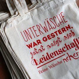 Jubiläums-Logo Parfümerie & Fotografie StraTypografisch gestaltete Stofftaschen für Neher Feine Wäsche. Rot auf helle Baumwolleuch Markdorf